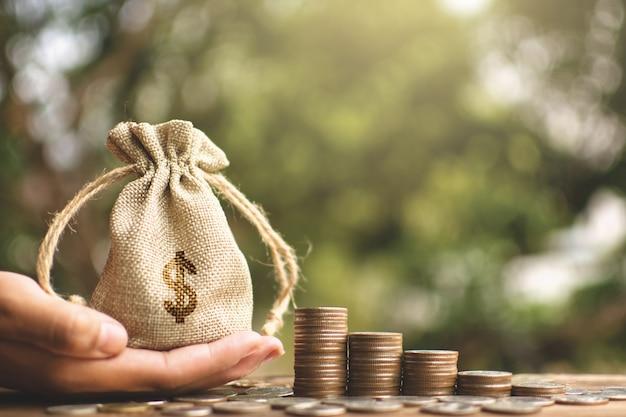 Женские руки держа сумку денег на предпосылке bokeh планки и дерева.
