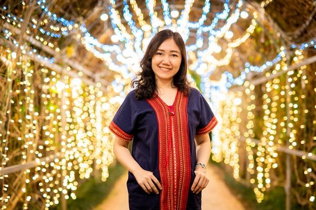 Красивая азиатско-тайская женщина в традиционном северном тайском платье представляя для фотоснимка в фестивале с красивой стеной bokeh освещения.