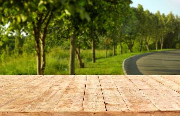 Макет. пустая деревянная таблица палубы с предпосылкой bokeh листвы.