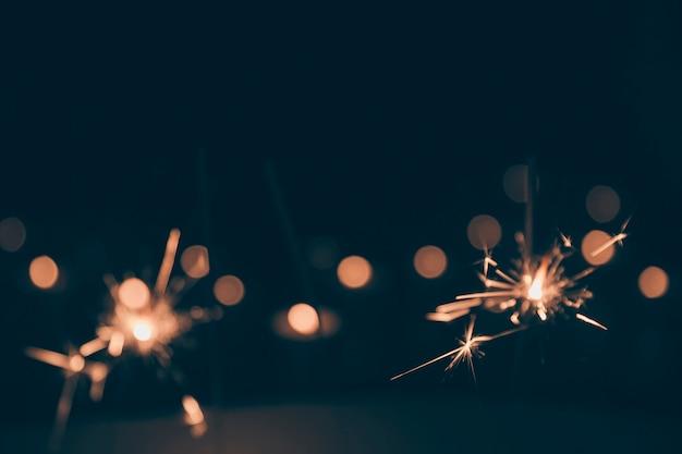 暗いbokehの背景で燃えている火花