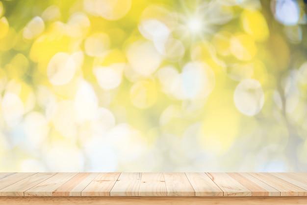 Bokeh黄色の背景と空の木製のテーブル。