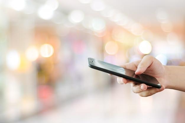 Рука используя смартфон над светом bokeh нерезкости, делом и технологией, интернетом концепции вещей