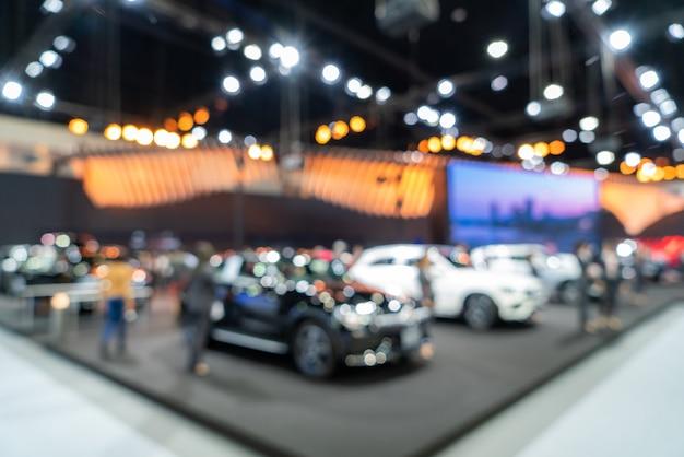 Запачканная предпосылка новых автомобилей показанных в роскошном выставочном зале с светлым bokeh, событии мотор-шоу.