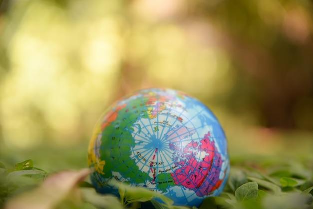 Шарик глобуса на естественном зеленом цвете выходит земля и зеленая предпосылка bokeh. концепция день окружающей среды мира.