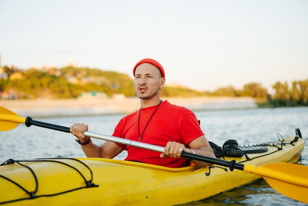 Bold man in orange watch cap and shirt riding on yellow kayak on a big wide river. reinforsed shoreline, trees and some houses in a distance.