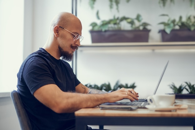 Bolded man with mustache and beard works on computer at home office programmer writer freeelancer