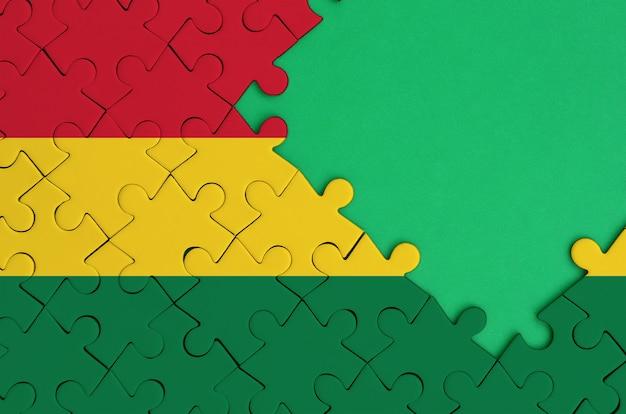 볼리비아 국기는 오른쪽에 무료 녹색 복사 공간이있는 완성 된 직소 퍼즐에 그려져 있습니다.