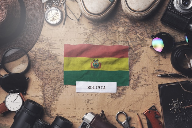 Bolivia flag between traveler's accessories on old vintage map. overhead shot