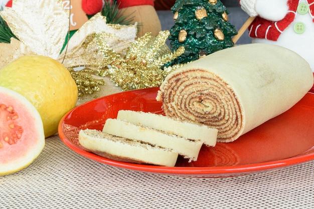 Боло-де-роло (рулет) рядом с гуавой и рождественским украшением.