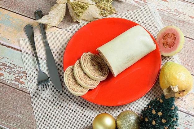 Боло-де-роло (рулетик) на красной тарелке рядом с рождественским украшением и гуавой.