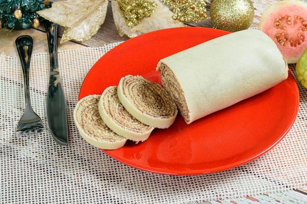 Боло-де-роло (рулет) нарезанный на красной тарелке рядом с рождественским украшением и гуавой.