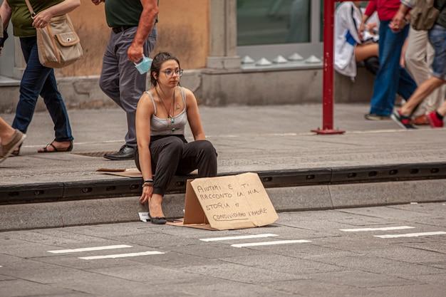 Bologna, italy 17 june 2020: girl begs on the sidewalk