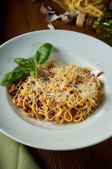 Паста болоньезе с красным соусом, пармезаном и мясным фаршем. итальянские спагетти с мясом в белой тарелке на деревянном фоне.