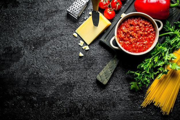 ドライパスタとチーズの入った鍋にボロネーゼソース