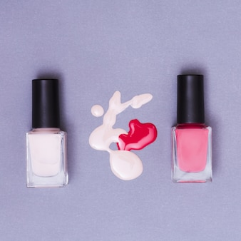 Bolt of pink and red nail polish bottles on purple backdrop