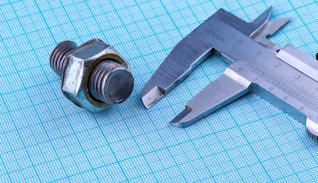 Bolt with nut and caliper on engineering paper.