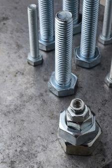 Болты и шестигранные гайки различных размеров, выложенные на металлической поверхности. разные крупные планы.