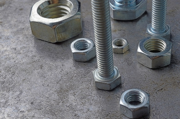 Bolts and hex nuts of various sizes, laid out on a metal surface