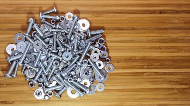 さまざまなサイズのボルト、ナット、ワッシャー、木製の竹製テーブル表面。テキスト用のスペースをコピーします。