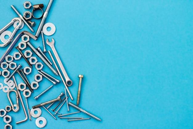 青い表面のボルト、ナット、レンチ、その他の建設ツール