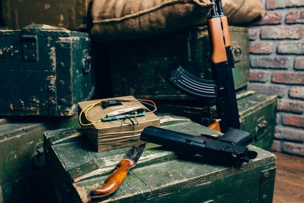 Bomb, knife, gun and rifle on box of ammunition