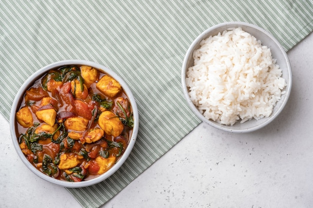 시금치, 토마토, 쌀을 곁들인 봄베이 치킨 카레