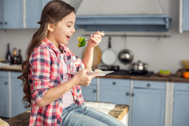 Bon appetit. beautiful cheerful dark-haired little girl smiling and sitting on the table and eating vegetables for breakfast