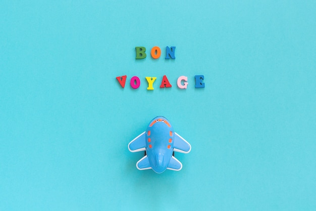 Bon voyage colorful text and children's funny toy plane on blue paper
