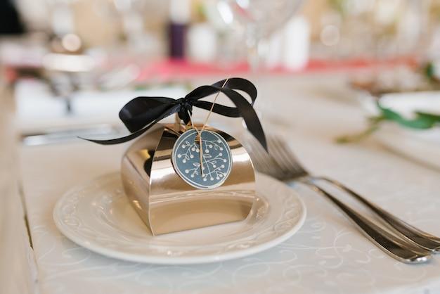 白いプレート上のbonbonniere golden、結婚式のディナーのサービング。結婚式の詳細