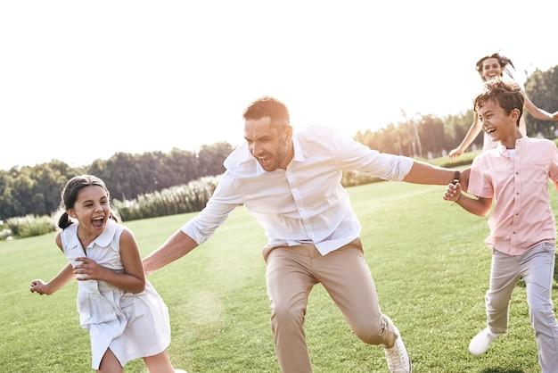 Семья из четырех человек работает на траве, играя в игру