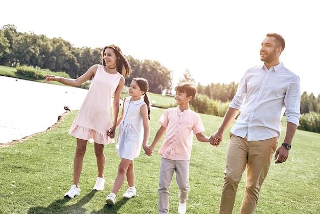 Семья из четырех человек гуляет по травянистому полю у озера