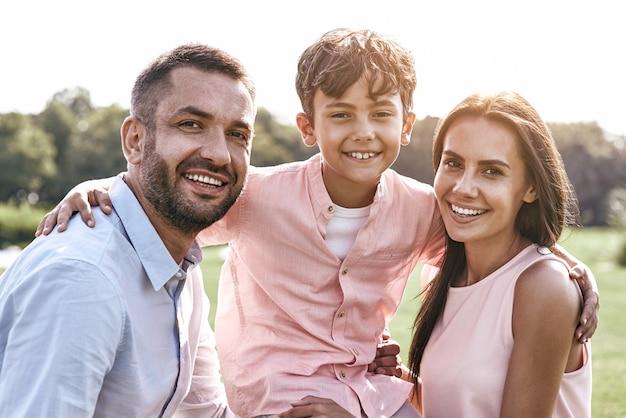 Семья из трех человек гуляет по траве и обнимает сына