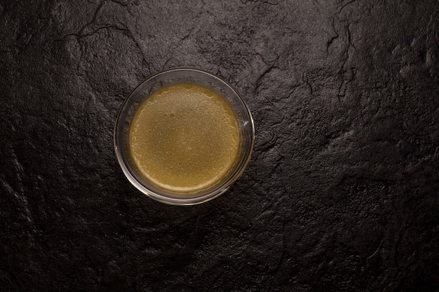 暗い石の表面にガラスの天然コラーゲンを含む骨ブロス。