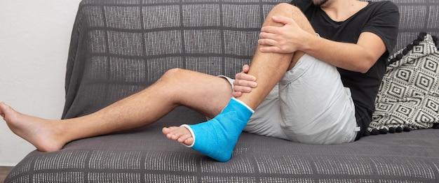 Стопа и нога перелома костей у пациента-мужчины и ортопедическое восстановление, лежа на диване, оставаясь на синей лодыжке шины.