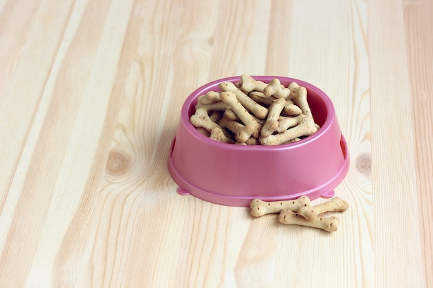 Bone-shaped biscuits in a pink plastic bowl
