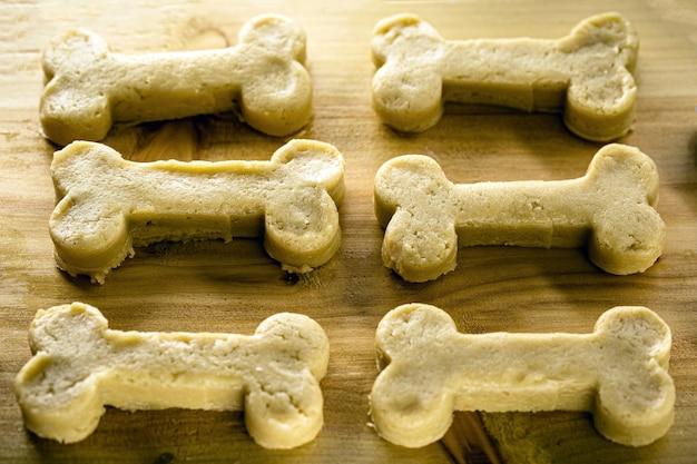調理されようとしている骨の形をしたクッキー、生の生地、自家製のペットのおやつ