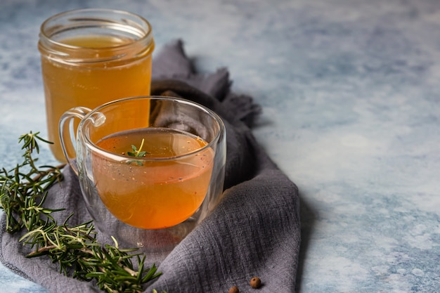 Bone or vegetable broth bouillon in a glass mug and aromatic herbs