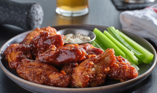 Куриные крылышки без костей, покрытые медово-чесночным соусом барбекю с ранчо и сельдереем