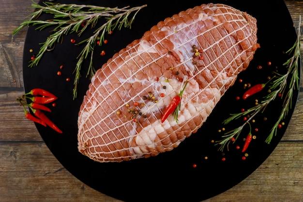 Свиная лопатка без костей со специями на черной деревянной доске. праздничная еда.