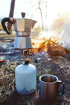 Костер и гейзерная кофеварка на переднем плане