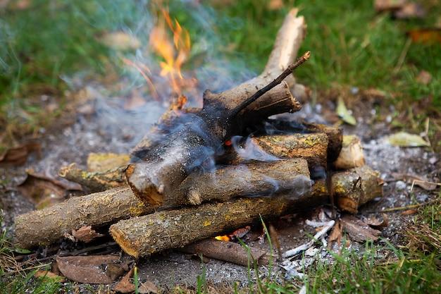 たき火、薪をクローズアップ。積み重ねられた丸太から燃える火