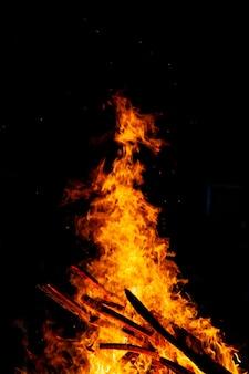 暗い背景で燃える焚き火、薪の炎。