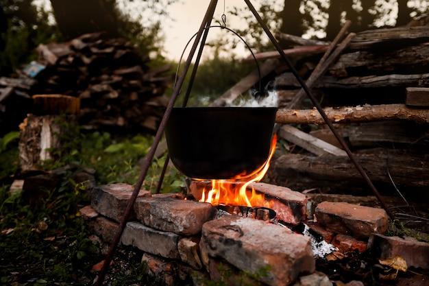 Костер с котелком для приготовления пищи ночью в лагере походы и кемпинг в лесу