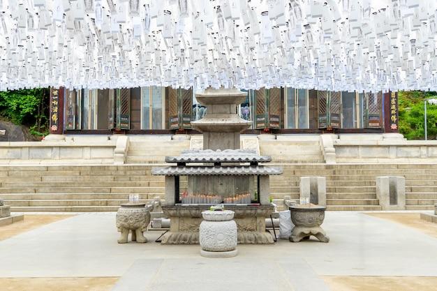 Храм бонгеунса в солнечный день под белыми фонарями и буддисты молятся будде в сеуле