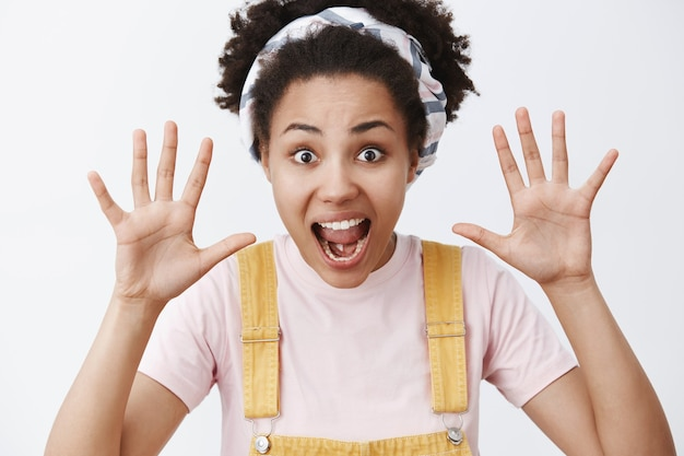 Boo. cute happy elder sister with dark skin in trendy yellow dungarees and headband raising palms and shouting, wanting scare sibling, standing childish over gray wall