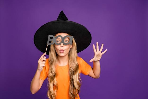 Бу! фотография маленькой ведьмы, играющей роль чародейки, на вечеринке в честь хэллоуина, держащей бумажную палочку, страшный вид, носить оранжевую футболку, шляпу волшебника, изолированный фиолетовый цвет фона