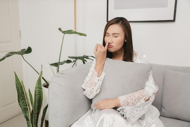 Boogers 흰색 새틴 잠옷을 입은 여인이 코 손가락을 집어 들었습니다.