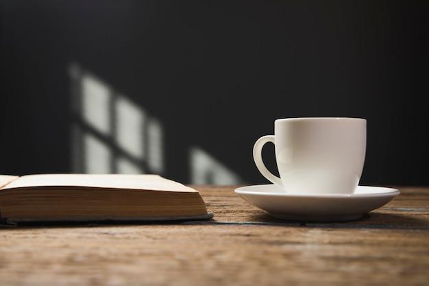 本と木製のテーブルの上のコーヒー