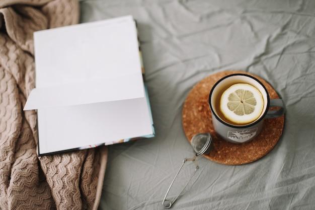 Книга и чашка чая с лимоном в теплой мягкой постели