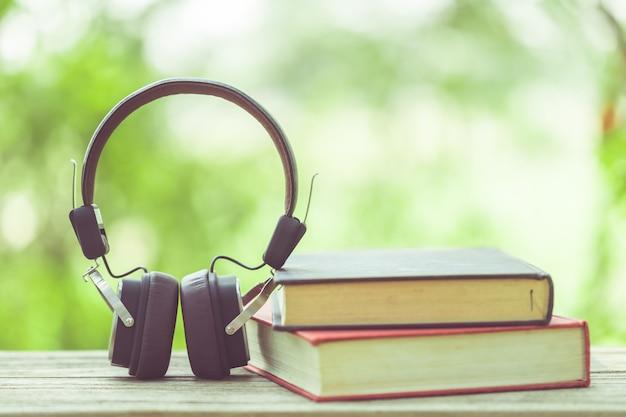 Запишите и черные наушники на деревянном столе с абстрактной зеленой нерезкостью природы. концепция чтения и образования